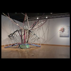 Untitled (ISO USD and backwards), 2012, Baltic birch, fabric, vinyl, wire, rope, light, 15' x 7' x 13'
