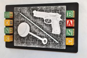 Gun Raffle, 2013, Found toy blocks, ink drawing on wooden puzzle on plywood