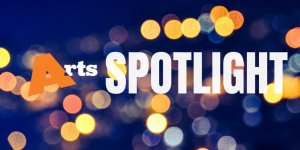 Arts Spotlight written on a dark blue background with unfocused orbs of light