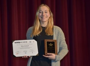 3/4 body portrait of Rebecca Wisniewski - 2021 Poetry Out Loud Winner holding her plaque and certificate in front of a red curtain