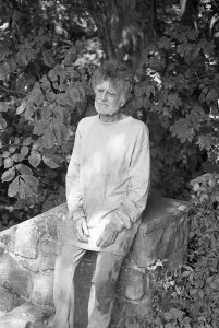 photograph of an old man leaning on a rock