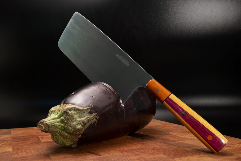 photograph of a knife in an eggplant