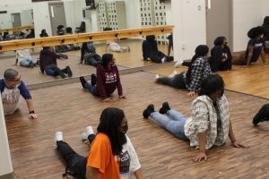 Group of teens stretching in a ballet studio on a wooden floor in front of a mirror on the wall