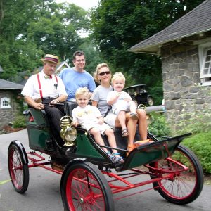 Family of four sitting in an antique automobile being driven by a man wearing period clothing on the grounds of the Marshall Steam Museum
