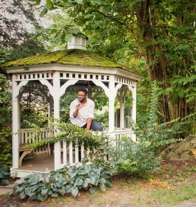 Man performing a scene of a play outside in a white, wooden gazebo with a moss-covered roof surrounded by trees and greenery