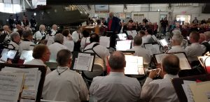 Group shot of the Milford Community Band from behind looking at the musicians' backs, music stands, and sheet music with the director and audience in the background. The band is playing in the Air Mobility Command Museum, a large, industrial building with unfinished, white walls with a military helicopter in the shot