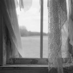 Artist Jason Jellick's black and white photograph of closed window looking out onto a field The window's paint is flaking and peeling. The window is surrounded by torn and tattered white curtains and lace sheers.