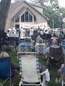 A band performs on an outdoor stage in a park in front of a brick building with rows of concert attendees sitting in lawn and folding chairs in front of the stage Concert goers are in the pictures foreground with their backs to the camera looking at the band