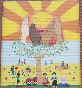 mural painted onto a red brick wall of adults and children enjoying the outdoors by playing reading biking etc on green grass in the foreground and yellow grass with flowers in the background all under a tree that reaches up and whose top branches become four hands of differing skin tones surrounding a bright yellow smiling sun